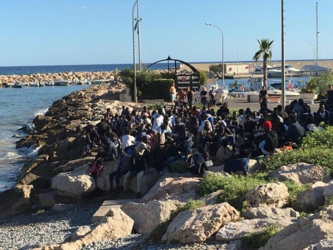 Un gruppo di migranti  di Ventimiglia scappati via mare hanno occupati gli scogli a Menton Garavan, su suolo francese ANSA/ TENERELLI